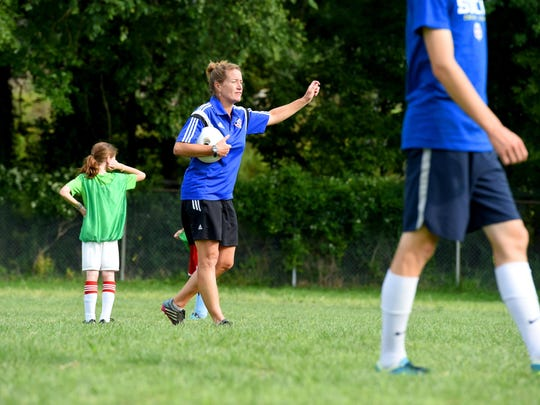 Ball in hand, SOCA Augusta Regional Director Nora Maquire White communicates with the young athletes during the last day of SOCA Augusta's preseason soccer camp in Staunton on August 13, 2015.