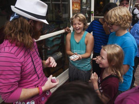 Austin Bannach laughs during a magic trick performed