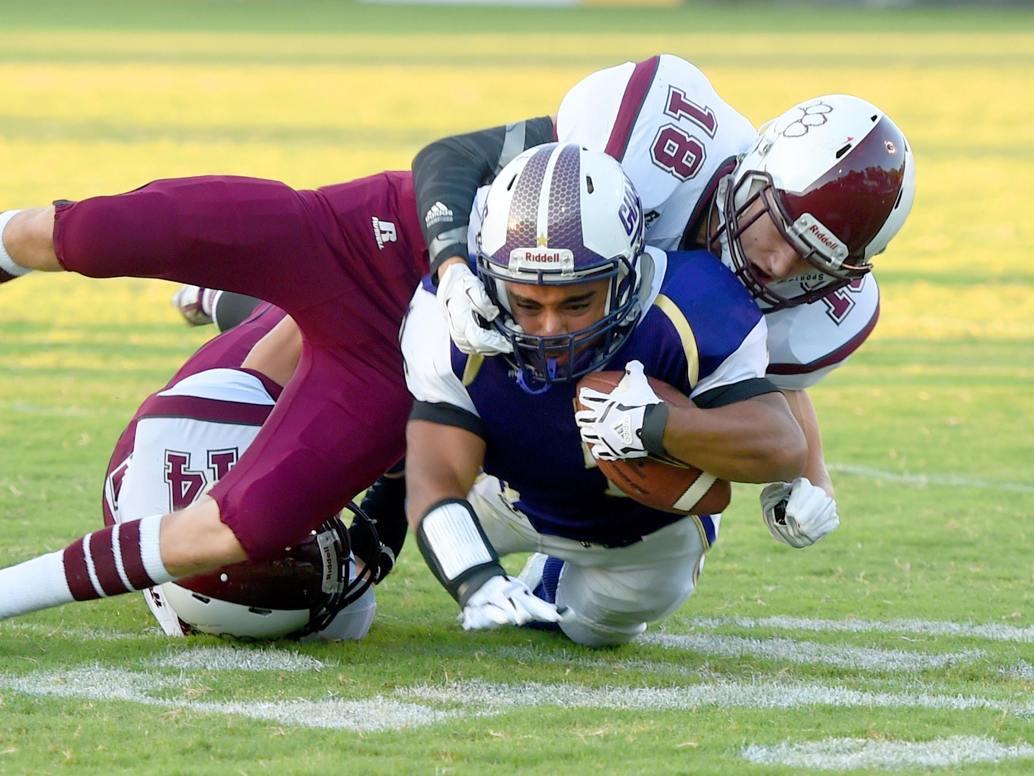 Waynesboro's Marendon Armon Jones is wrapped up by Stuarts Draft's Colton Stiltner and Trevor Craig who rbring him down during a football game played in Waynesboro on Friday, Sept. 11, 2015.