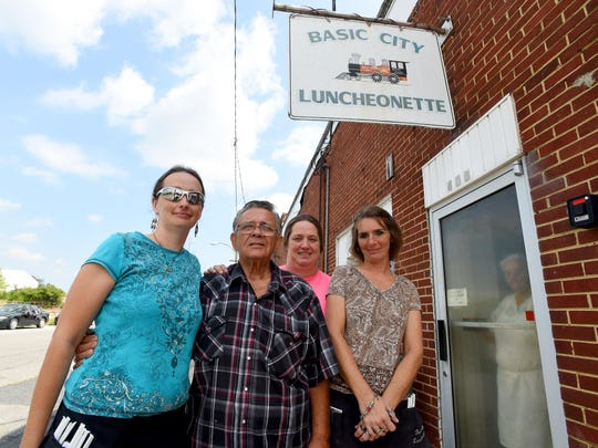 Butch Dean, owner of Basic City Luncheonette, stands with waitresses Heather Harris, Cheryl Russell and Beck Phillips, the three of whom are sisters, outside the restaurant in Waynesboro on Friday, August 28, 2015. Brenda Leavell peeks out from the door as the photograph is being taken.