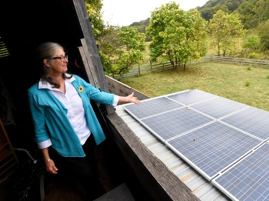 Sandy Greene looks out over the solar panels installed on a lower roof of her barn, which helps provide electricity to her Augusta County residence, on Tuesday, Sept. 22, 2015.