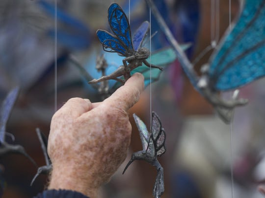 An attendee at the Fall Foliage Festival Art Show in downtown Waynesboro examines a small piece of glass and metal art on Oct. 11, 2014.