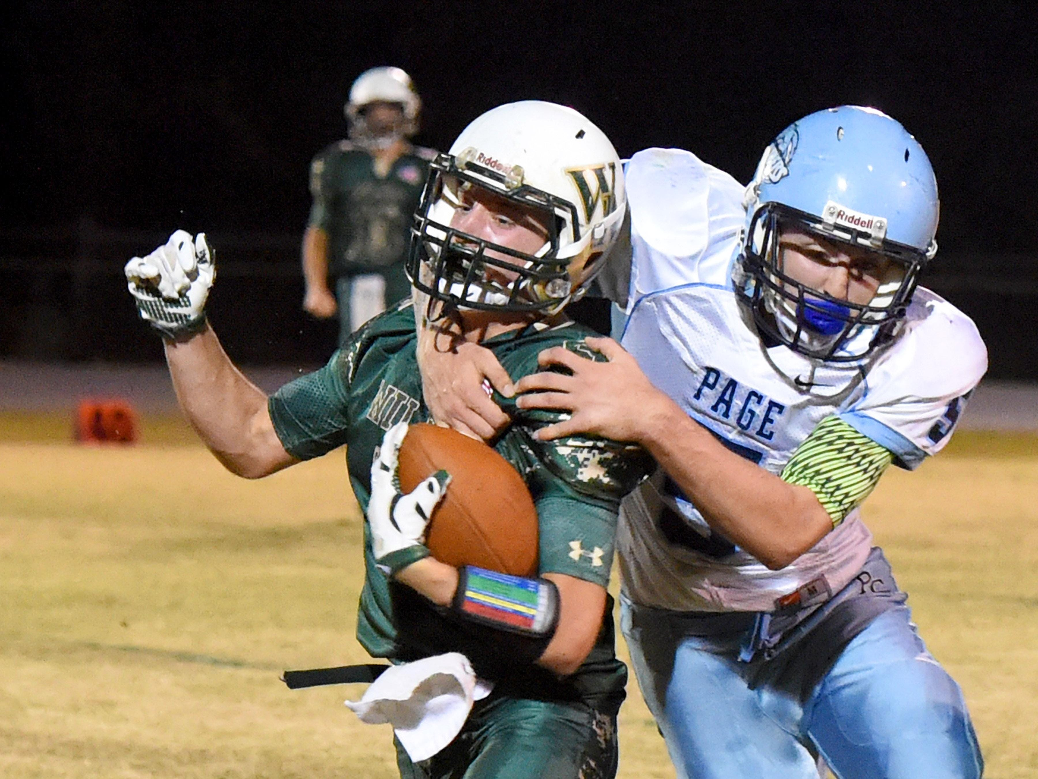 Page County's Bailey Turner grabs Wilson Memorial's Kyle Coombe during a their game in Fishersville on Friday.