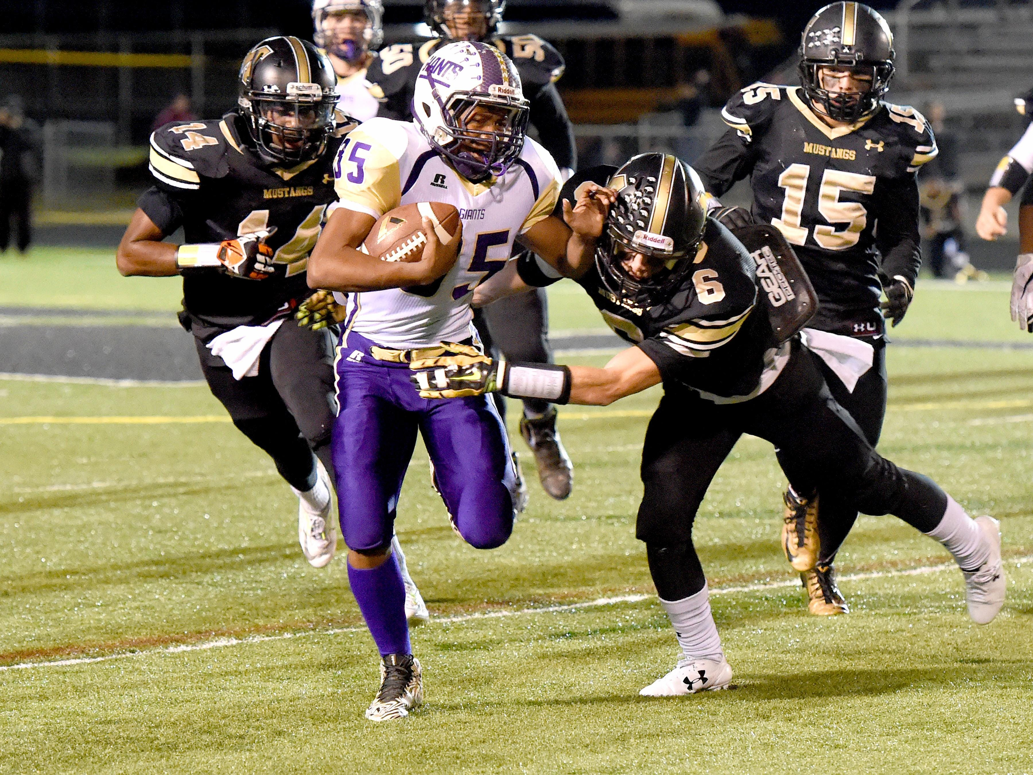 Waynesboro's Delano Green Jr. runs the football as Montecello's Seth Weaver goes for the tackle with Syrael Breckenridge and Garrett Porterfield just behind during a 3A West regional football game played in Charlottesville on Friday, Nov. 13, 2015.