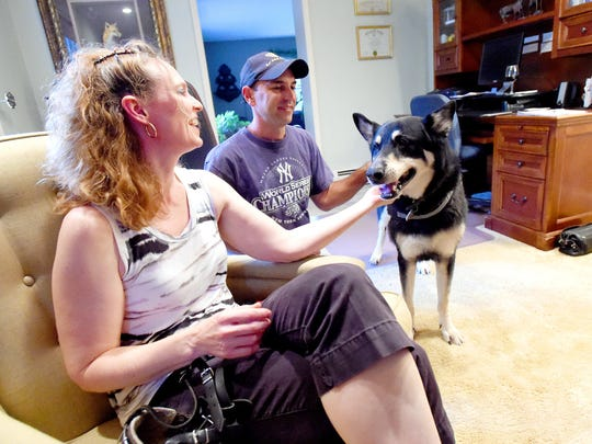 Apollo, a German shepherd, shares a bond with his owners, Heather and Scott Fox. They spend time in their home just before heading out for their evening walk around their neighborhood in Waynesboro on July 20, 2016.