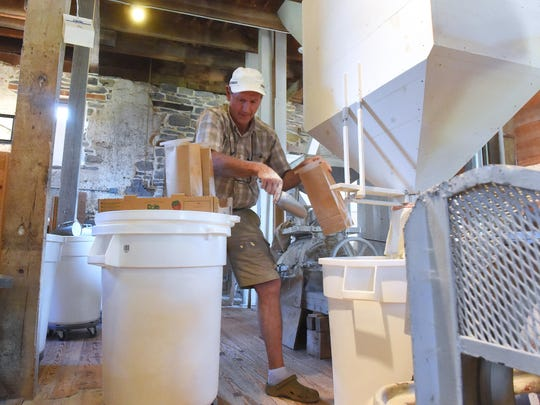 """Everything I do is completely new and different from what I was doing before, and it's fun for that reason,"" said John Siegfried. ""I was in the oil and gas business for 35 years, working overseas … lots of different countries.""  He bags flour being freshly ground by a Meadows stone burr mill inside Wade's Mill"