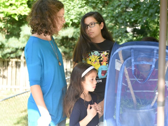 Sarah Roberson (left) speaks with her 12-year-old daughter Margaret Carbajal while 7-year-old daughter Charlotte Carbajal looks into their small enclosure. They study the life cycle of caterpillars and butterflies outside their home in Staunton on Sept. 6, 2016.