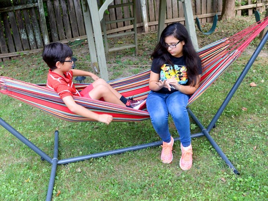 Logan Carbajal, 10, shares a hammock with his 12-year-old sister, Margaret Carbajal, as they spend time in their family's backyard in Staunton on Sept. 6, 2016.
