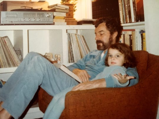 Sarah Roberson sits with her father, Bill Roberson, in an undated photo of her as a child.