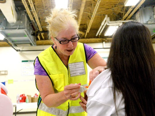 Registered nurse Fonda Cassidy of the Virginia Department of Health administers a flu vaccination to an individual who walked into the free clinic held at the Dixon Education Center on Friday, Oct. 24, 2014. The VDH's Central Shenandoah Health District conducted the free flu vaccination clinic as a test of their emergency dispensing plans.