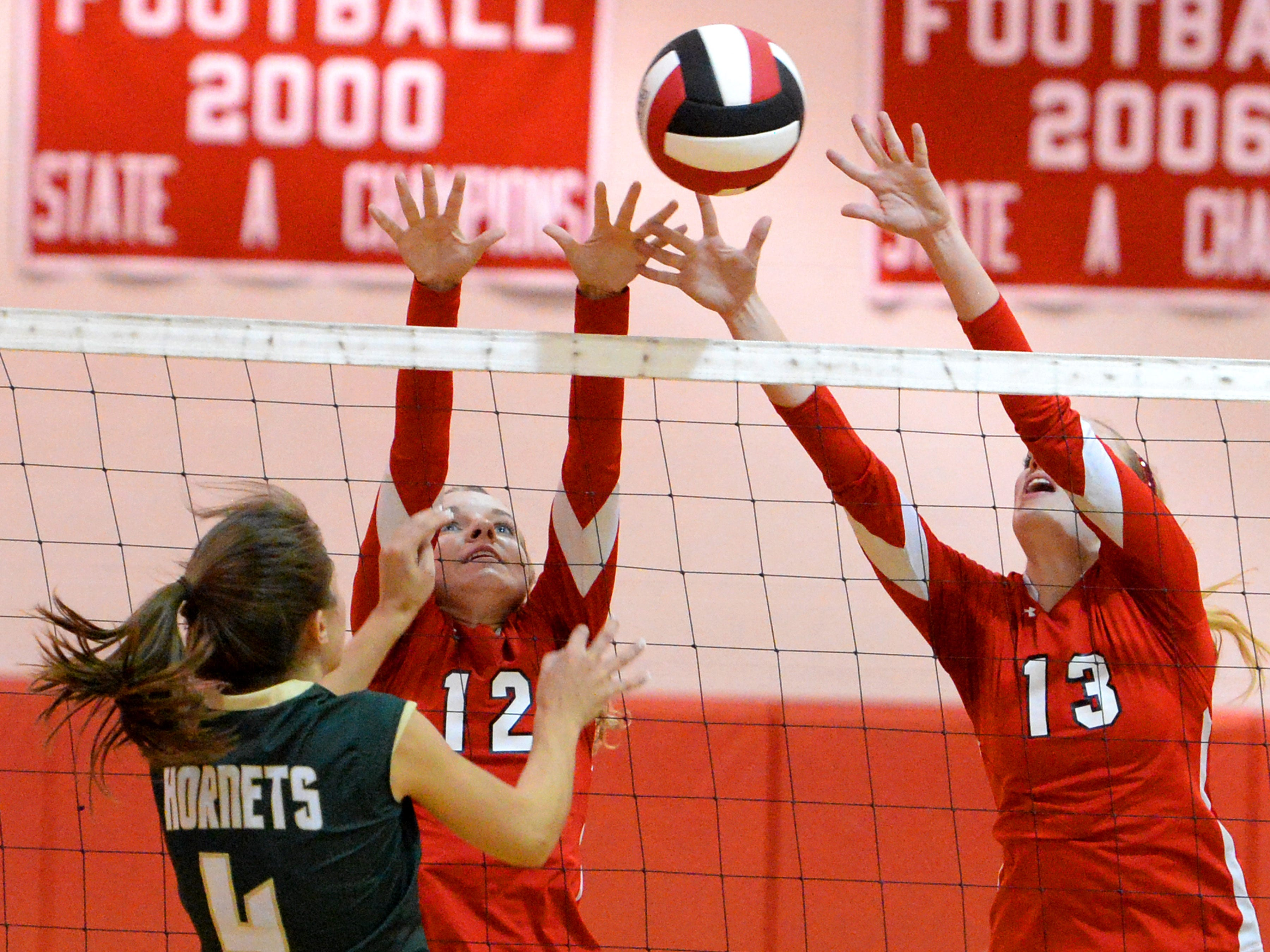 Riverheads' Mekayla Heizer, left, and Mariah Clark attempt to block a return by Wilson Memorial's Alison Eskridge during their Conference 36 championship match in Greenville on Thursday. The Gladiators swept the Green Hornets for the title.
