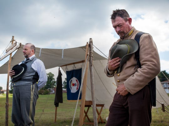 John Freeman, right, playing a Confederate Civil War soldier from the 10th Regiment, Virginia Cavalry, bows his head during a prayer before the start of the reenactment to commemorate the 150th and 149th anniversaries of the first and second battles of Waynesboro at Coyner Springs Park on Sunday, Aug. 31, 2014.