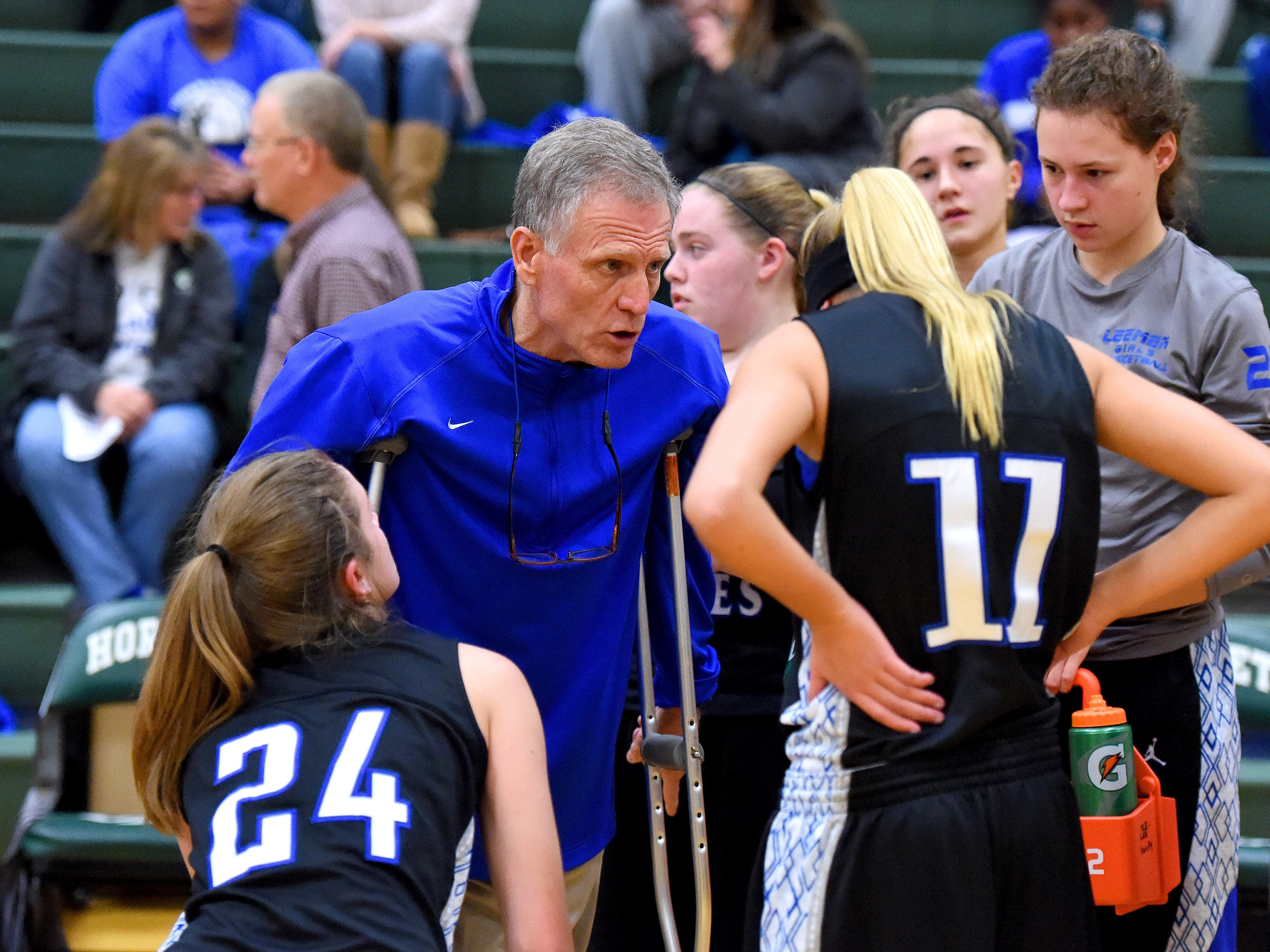 Robert E. Lee head coach Dennis Dull stands with crutches as he speaks with his team during a timeout in their basketball game against Wilson Memorial on Dec. 15.