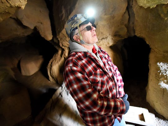 Making use of the light on his helmet, avid caver Phil Lucas talks about his own efforts in exploring Water Sinks Cave in Highland County during an interview on Thursday, Feb. 12, 2015.