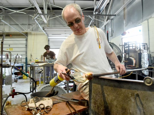 Glassblower Daniel Scogna uses a blowtorch to help shape his creation while fellow artist Seth Hendrick works on another piece.