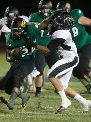 Saguaro's Kamron Johnson breaks through a tackle from Williams Field's Tim Polanco on his way to a touchdown at Scottsdale Saguaro High School on Thursday, Oct. 9, 2014.