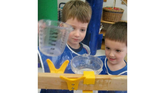 Caleb Rittenhouse and Colton Blawat, JK4 students, explore their interests related to the properties of water using Funnel Water Play at University Lake School.