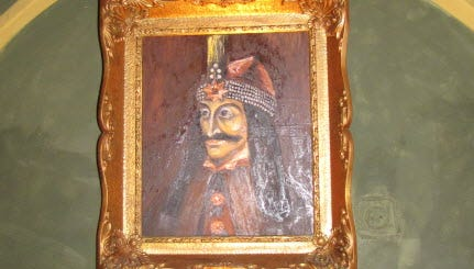 A portrait of Vlad the Impaler hanging in a restaurant.