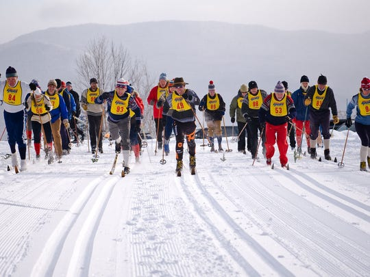 Today's skiers race each other while sporting the equipment of yesteryear.