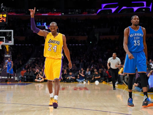 Los Angeles Lakers forward Kobe Bryant, left, gestures after scoring as Oklahoma City Thunder forward Kevin Durant walks next to him during the first half of an NBA basketball game Friday, Jan. 8, 2016, in Los Angeles. (AP Photo/Mark J. Terrill)