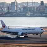 A Japan Airlines Boeing 777 aircraft lands Jan. 28, 2016,  at Tokyo's Haneda Airport.