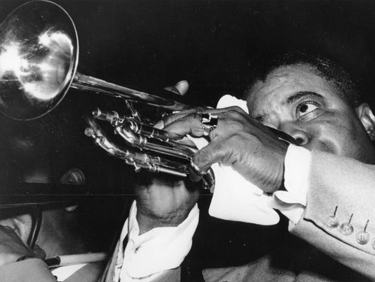 American jazz musician Louis Armstrong plays his trumpet
