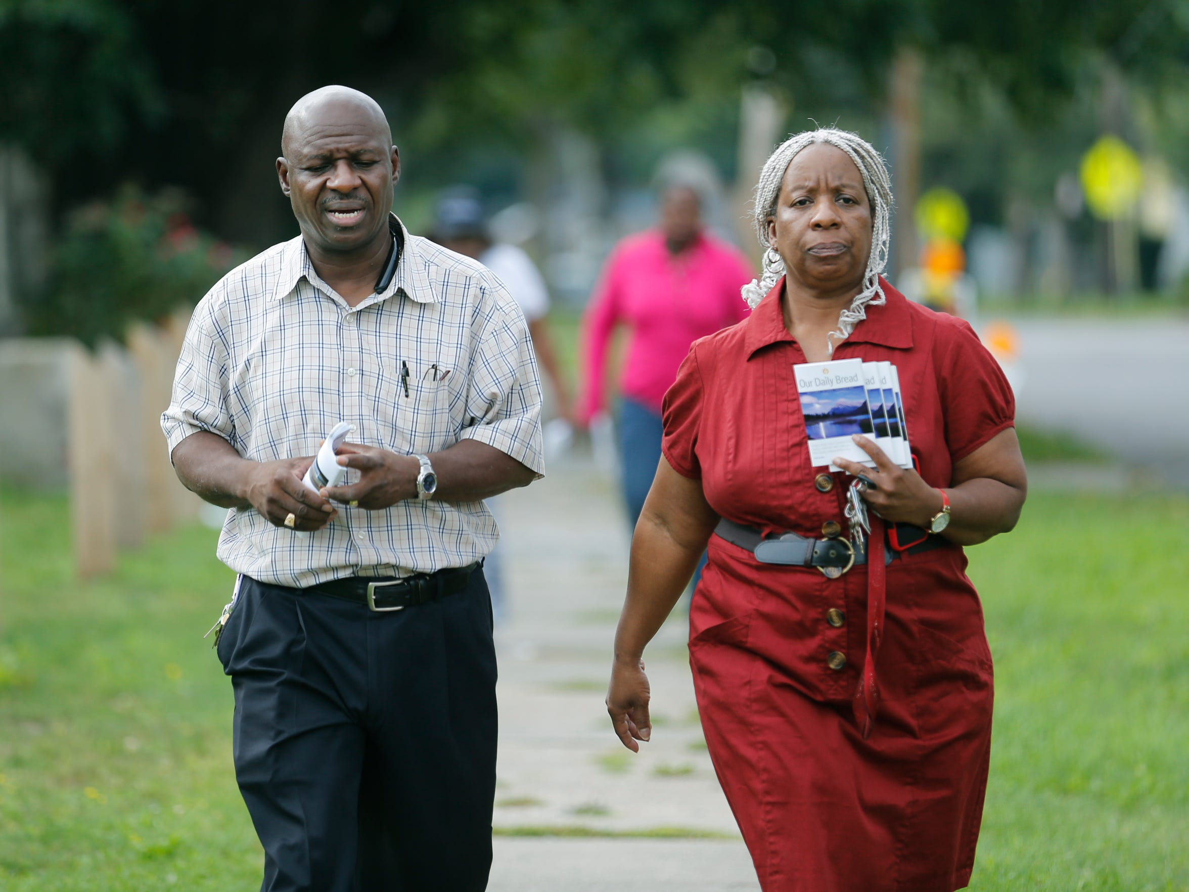 Bishop David Singleton, pastor of the Ark of Jesus Ministry, and his sister Susan walk with others from house to house to talk to neighbors after a summer of violence.