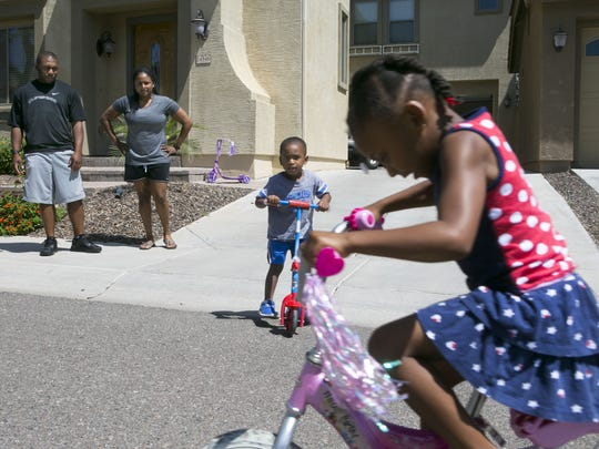 Mia Corley, 5, and Aiden Corley, 3, play on their bikes and scooters as their parents, Marcus Corley and Air Force Sr. Airman Kim Corley, look on in the street in front of their home in Surprise.