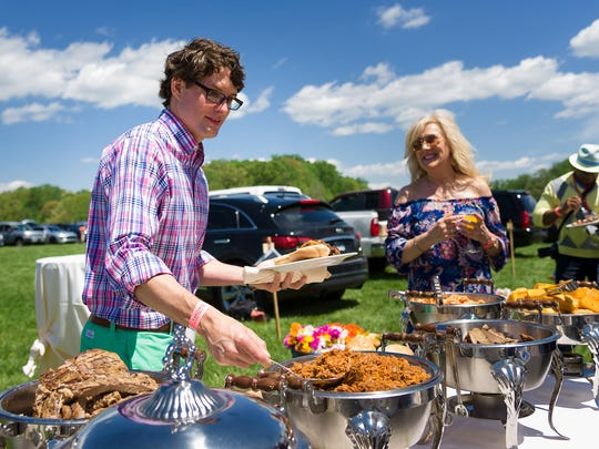 Matt Axe of Hockessin digs into food at a tailgate at last spring's Point to Point.