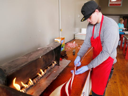 A gas flame keeps the sugar for candy canes malleable