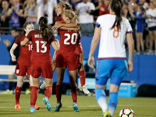 U.S. midfielder Allie Long (20) hugs Mallory Pugh as they celebrate a goal by Long with Rose Lavelle (16) and Alex Morgan (13) in the second half of an international friendly soccer match against Russia in Frisco, Texas, Thursday, April 6, 2017. Russia defender Daria Makarenko (8) walks by. (AP Photo/Tony Gutierrez)