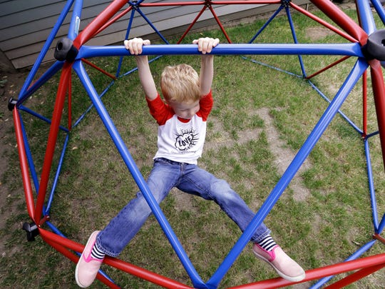 Declan Hartman, 4, clambers on a climbing toy as he wears a gender-neutral T-shirt designed by his mother, and his favorite pink shoes,