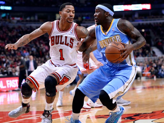Denver Nuggets point guard Ty Lawson (3) dribbles the ball against Chicago Bulls point guard Derrick Rose (1) during the first quarter at the United Center.