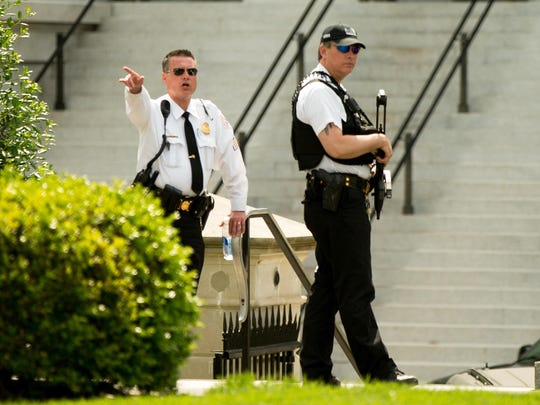 A Secret Service agent orders people into buildings near the entrance to the West Wing of the White House in Washington, Friday, May 20, 2016, after the White House was placed on security alert after shooting on street outside.