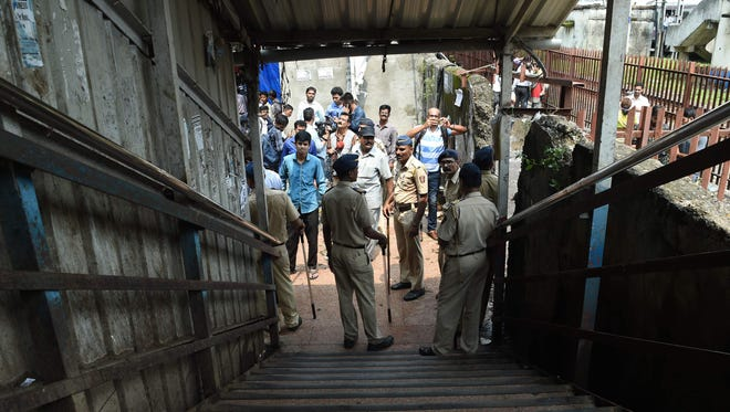 Indian security personnel and media gather at the scene of a stampede on a railway bridge in Mumbai on Sept. 29, 2017.