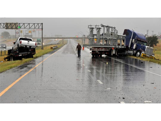 A jackknifed 18-wheeler and a trailer rest on both shoulders of the westbound side of Interstate 20 Tuesday Sept. 26, 2017.