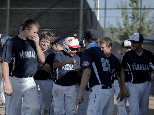 Visalia's Roland Luna is congratulated by teammates after hiting a home run against Hanford.
