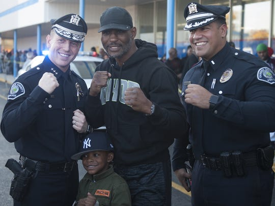 Philadelphia Boxing Champion Bernard Hopkins, center , with his son, Bernard Hopkins III,  poses for a photo with Police Chief J. Scott Thomson, left, and Lt. Gabriel Rodriguez during a visit to Price Rite of Camden. the boxer donated more than 600 Turkeys to Camden Residents
