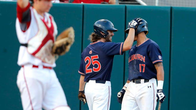 Auburn's Jay Estes (25) celebrates with Will Holland (17) after Estes scored in the third inning during N.C. State's college baseball game against Auburn in the Raleigh Regional at Doak Field in Raleigh, N.C., Sunday, June 3, 2018.