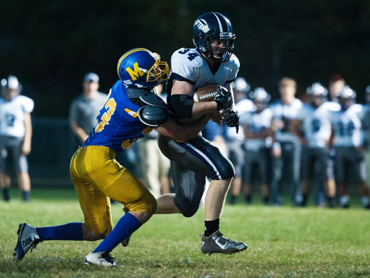 Otter Valley's Carson Leary, right, is tackled by Milton's