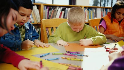 Children (8-10) coloring with crayons at table in classroom. Credit: Getty Images
