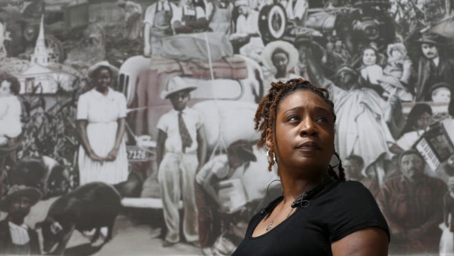 "Waterloo resident Doris Dedrick stands in front of the fading outdoor mural ""Keki Me Si Metose Neniwa,"" or ""We The People,"" that depicts the blending of cultures in Waterloo. Dedrick said she has been pulled over multiple times by police, and feels she is being targeted because of her race."