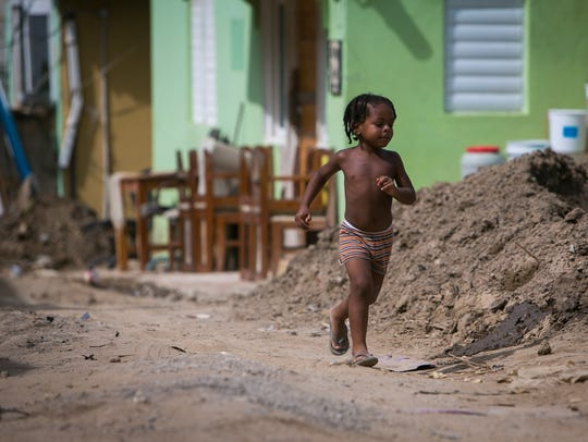 A local girl runs by piles of mud in the village of