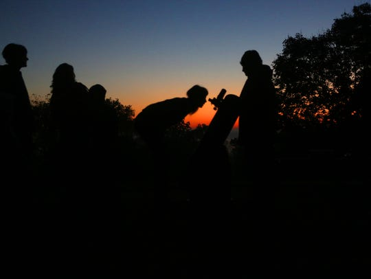 People view the lunar eclipse through a telescope as