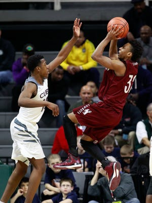 Detroit Western's Josh McFolley shoots over University of Detroit Jesuit's Obi Duru in the second half of their MHSAA boys Class A semifinal basketball game on Friday, March 27, 2015 in East Lansing.