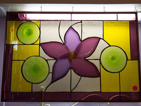 Green plates dance around a purple flower in this $225 stained glass panel by Gwenn Schroll of Millsboro.