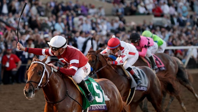 Florent Geroux, left, rides Gun Runner to victory in the Classic horse race during the Breeders' Cup, Saturday, Nov. 4, 2017, in Del Mar, Calif. (AP Photo/Gregory Bull)