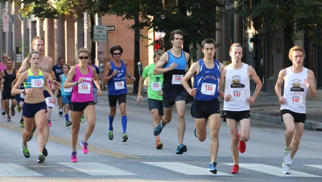 Runners hustle down George Street in York city during the 8th Annual Quarterback Club of York 10K & 5K on Sunday. For results from the races, see Page 5B.