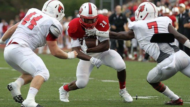 La Salle running back Jeremy Larkin (28) takes on two defenders in the first half during the high school football game between La Salle and Colerain, Friday, Sept. 11, 2015, at La Salle High School.