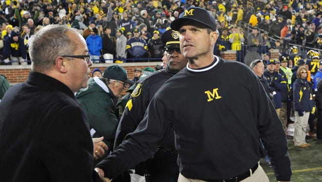 Michigan head coach Jim Harbaugh stops to shake hands with Michigan State Athletic Director Mark Hollis after failing to locate MSU head coach Mark Dantonio for the customary postgame handshake after a shocking reversal of fortunes on the final play of the game led to an MSU victory 27-23.